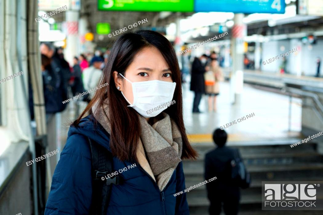 Stock Photo: Woman wear face mask in train station.