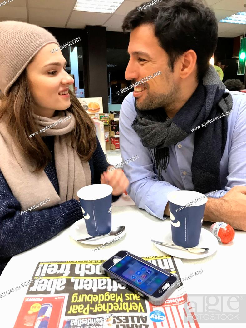 Imagen: couple looking at each other, taking a break at table at gas station's café with newspaper Bild and phone laying on table and paper cups of coffee in Munich.