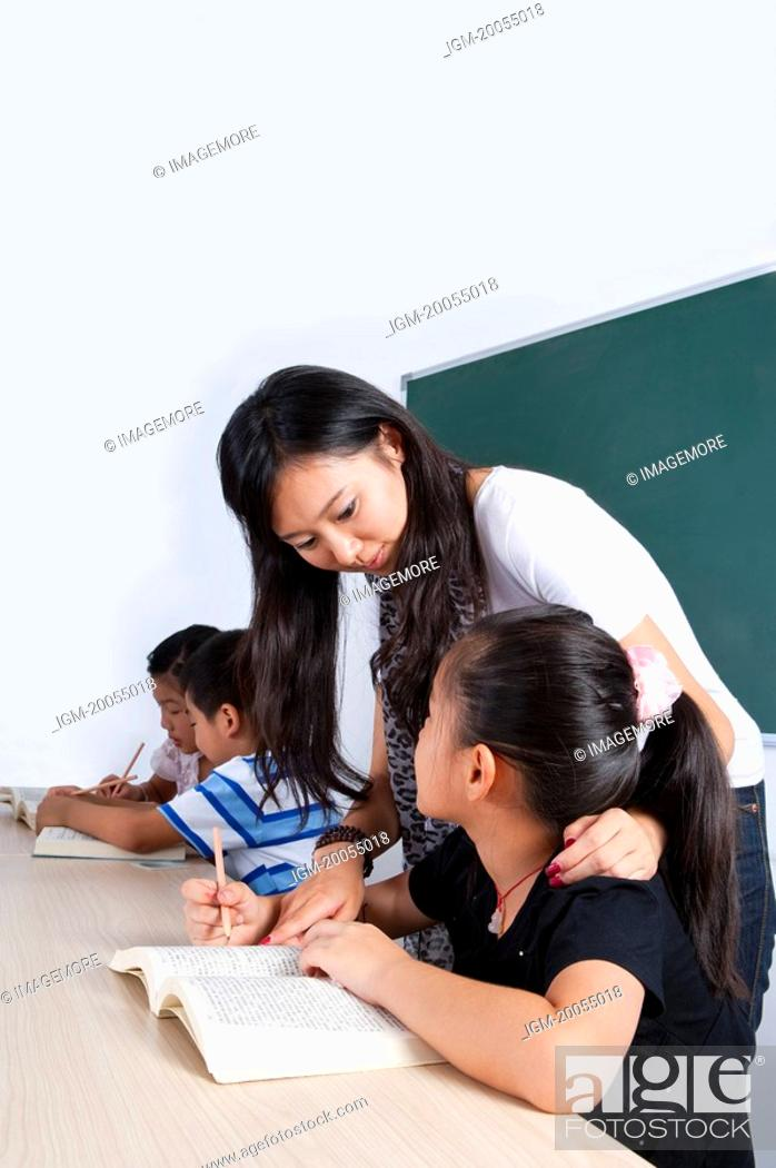 Stock Photo: Child, Young teacher teaching children in the classroom.