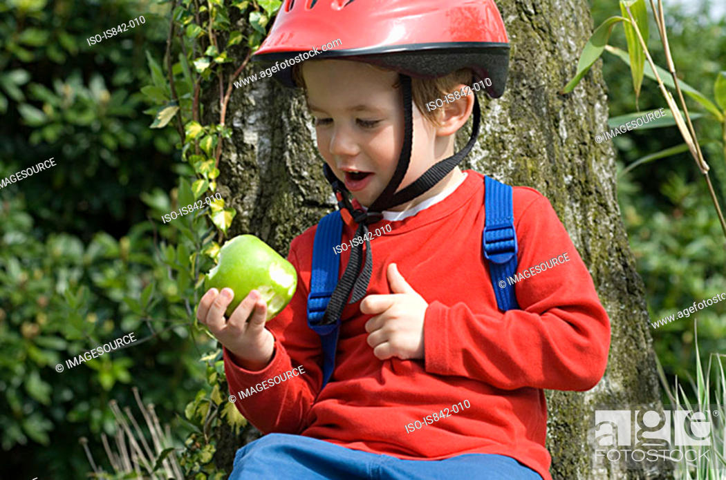 Stock Photo: Boy in a bike helmet with an apple.