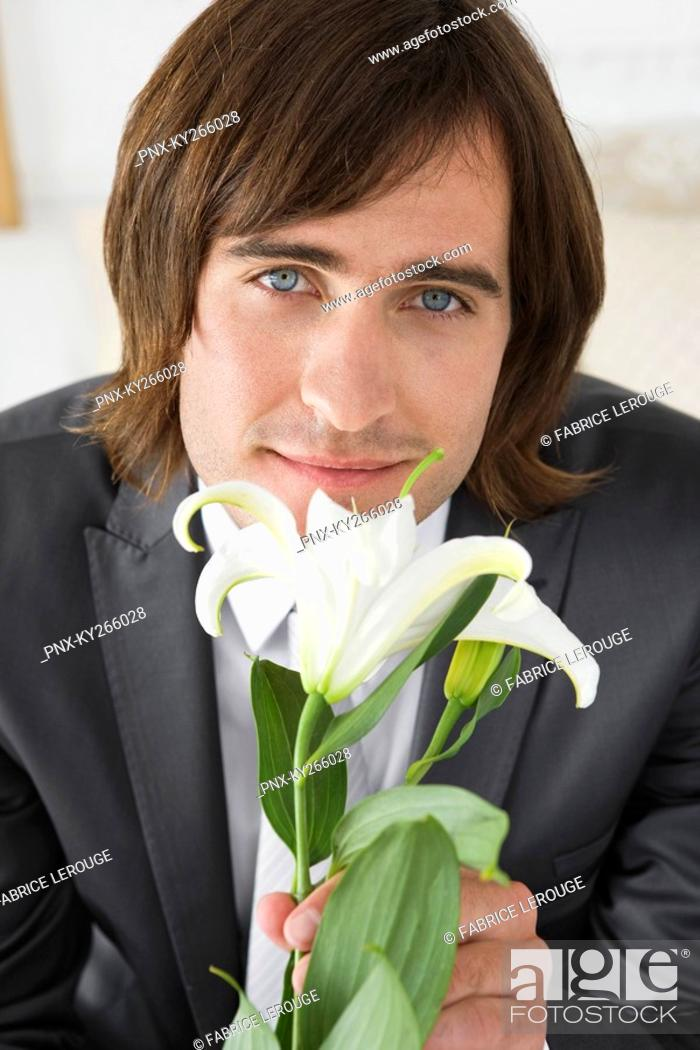 Imagen: Groom sitting on the bed and holding a lily flower.