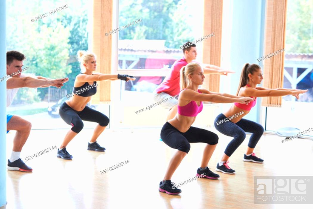 Stock Photo: Group of people exercising at the gym and stretching.