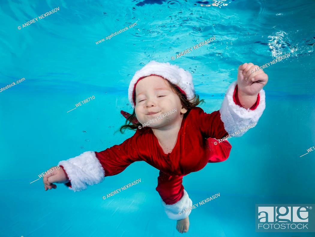 Imagen: Funny long-haired boy in a Christmas outfit dives underwater in a swimming pool.