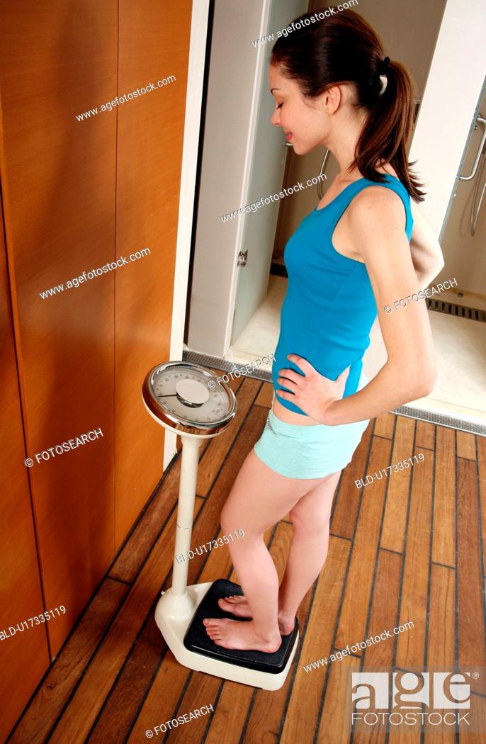 Stock Photo: Woman weighing herself on scales in the locker room.