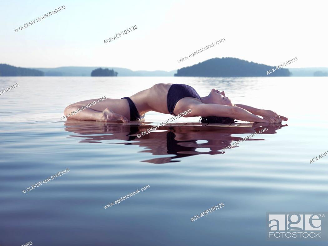 Stock Photo: Young woman practicing sunrise yoga on a platform in calm water on the lake during misty morning. Yoga Fish posture, Matsyasana.