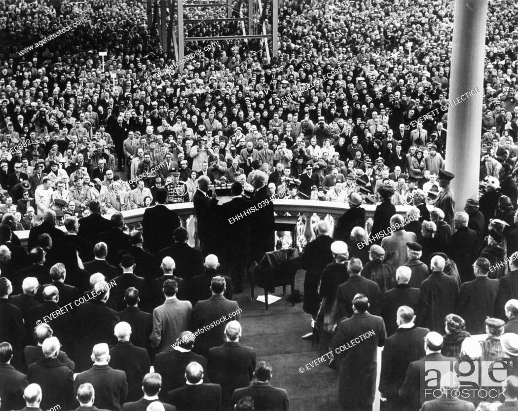 Stock Photo: President Eisenhower sworn in by Chief Justice Earl Warren at the public Inauguration. Photo is taken from the back of the Inaugural stage showing the crowd.