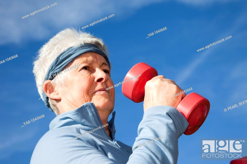 Stock Photo: Britain, UK, Europe  Senior woman exercising with dumbbell hand weights outdoors  MR 10/02.