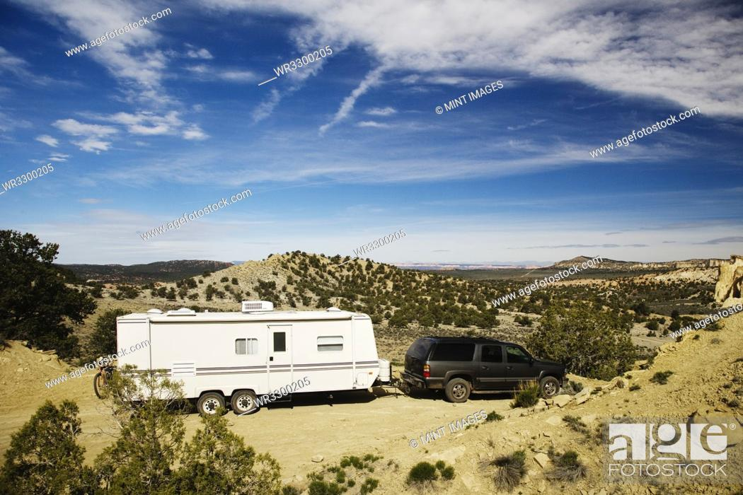 Stock Photo: Car pulling trailer in desert landscape, Grand Staircase Escalante, Utah, United States.