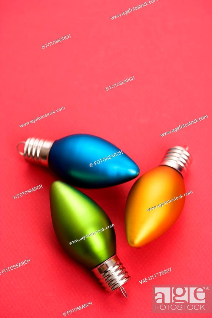 Stock Photo: Still life of blue, green and orange Christmas ornaments on red background.