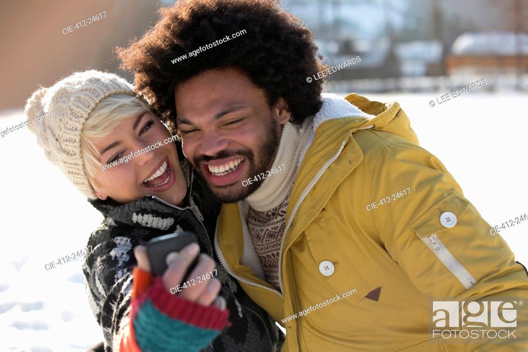 Photo de stock: Happy couple taking selfie in snow.