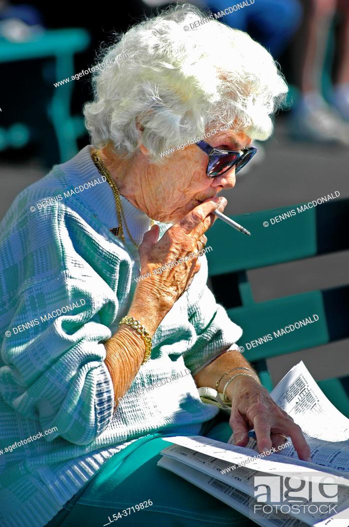 Imagen: old woman smoking a cigarette outside.