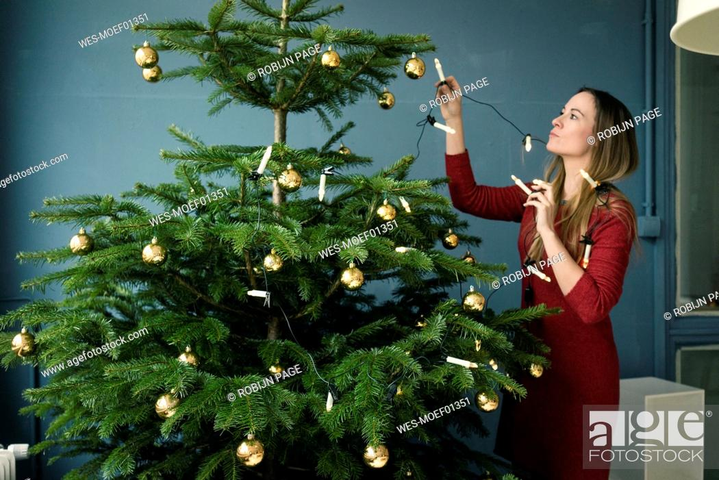 Stock Photo: Woman decorating Christmas tree.