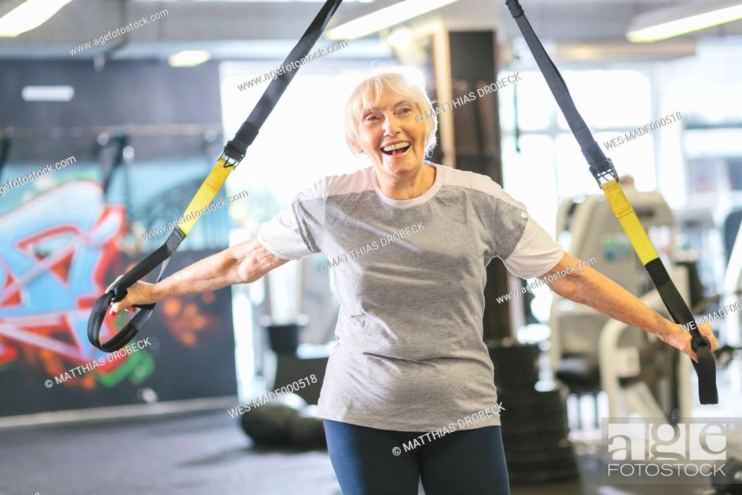 Stock Photo: Happy senior woman in gym doing suspension training.