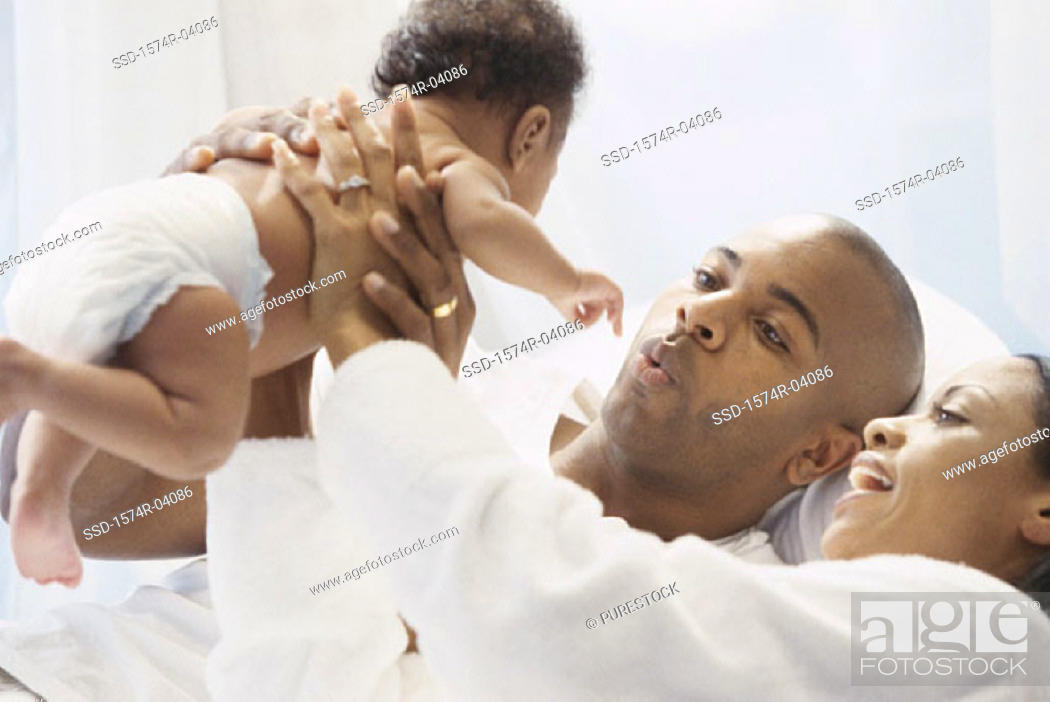 Stock Photo: Parents holding their baby boy.