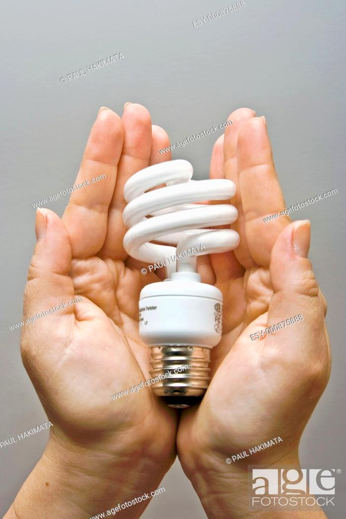Stock Photo: Two female hands presenting an environmental friendly and power saving fluorescent light bulb.