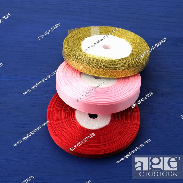 Stock Photo: twisted red, pink, golden silk ribbons on a blue background, element for the designer, close up.
