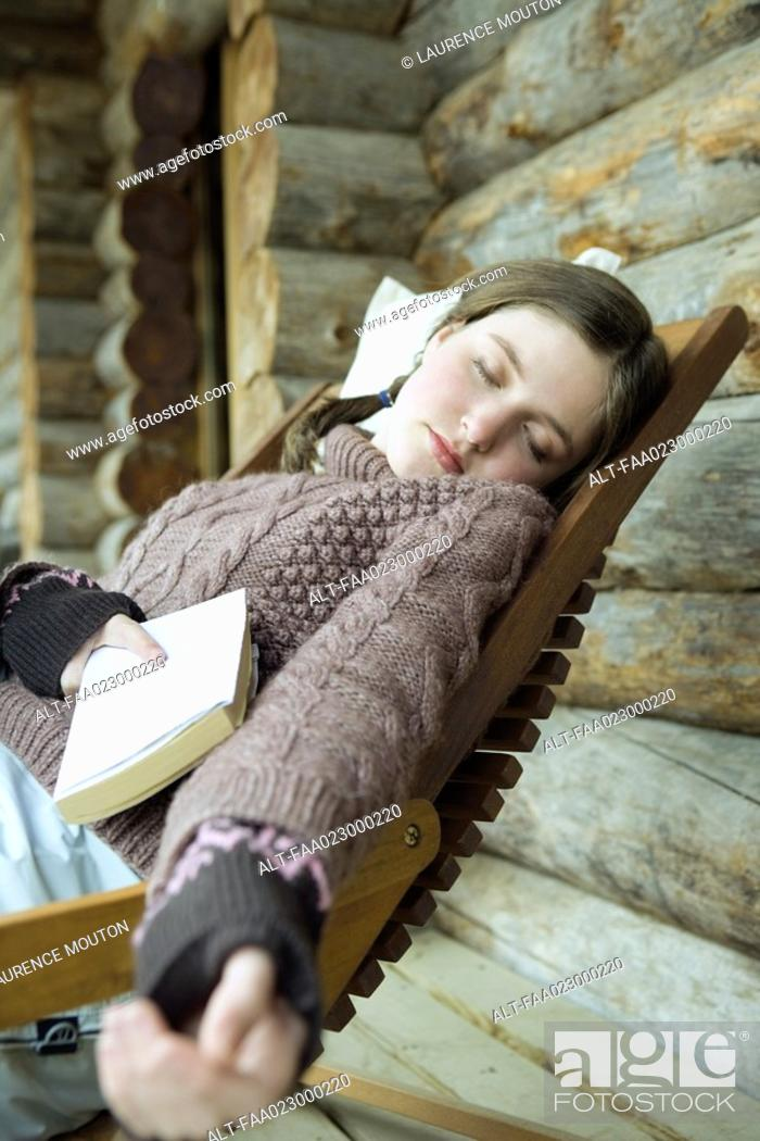 Stock Photo: Teen girl in winter clothes, falling asleep while holding book.