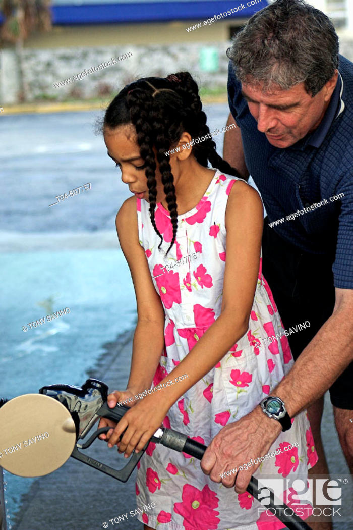 Stock Photo: 10-year-old biracial girl pumping gasolean with middle-aged man. Miami Beach, Florida, USA.