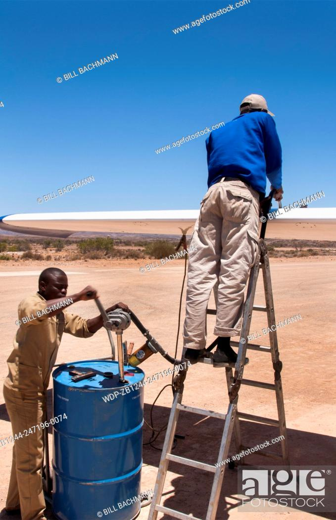 Imagen: Namibia Namib Desert refueling plane in the Hartmann Berge Marienflub sand remote landing strip with workers pumping manually fuel gas.