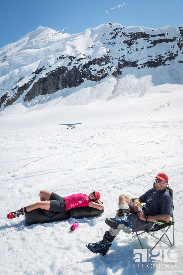 Imagen: A couple relaxes while awaiting a ski plane pick up on the Ruth Glacier in the Alaska Range, Summer.