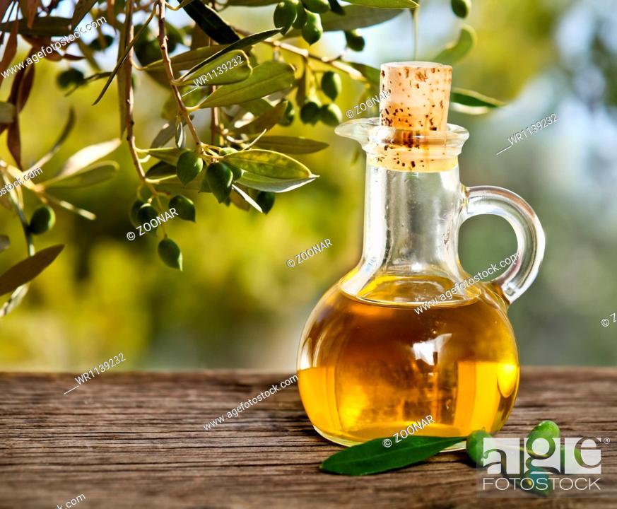 Stock Photo: Olive oil and olive branch on the wooden table.