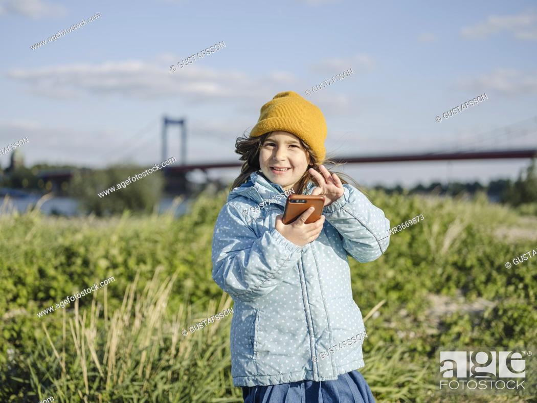 Stock Photo: Cute smiling girl using smart phone while standing on land against sky.