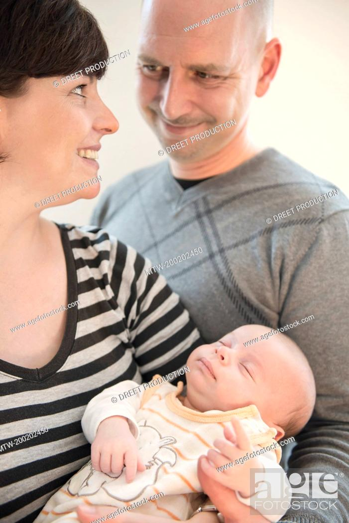 Imagen: Parents holding their baby boy in arms, smiling.