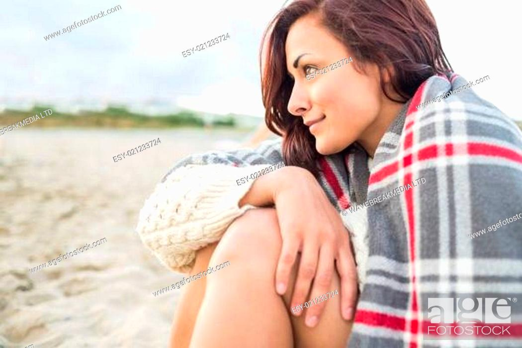 Stock Photo: Side view of woman covered with blanket at beach.