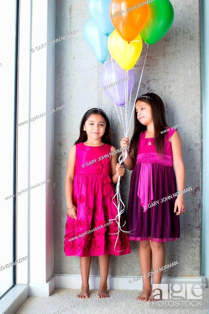 Stock Photo: Portrait two young girls holding balloons.
