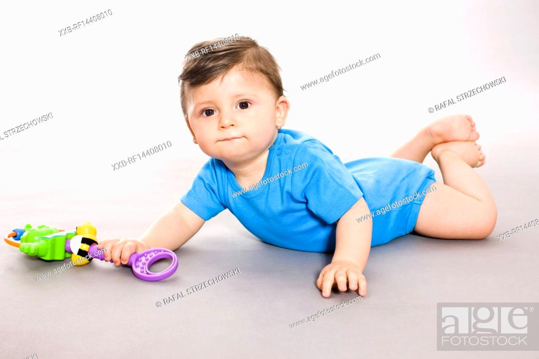 Stock Photo: Baby on floor with toy.