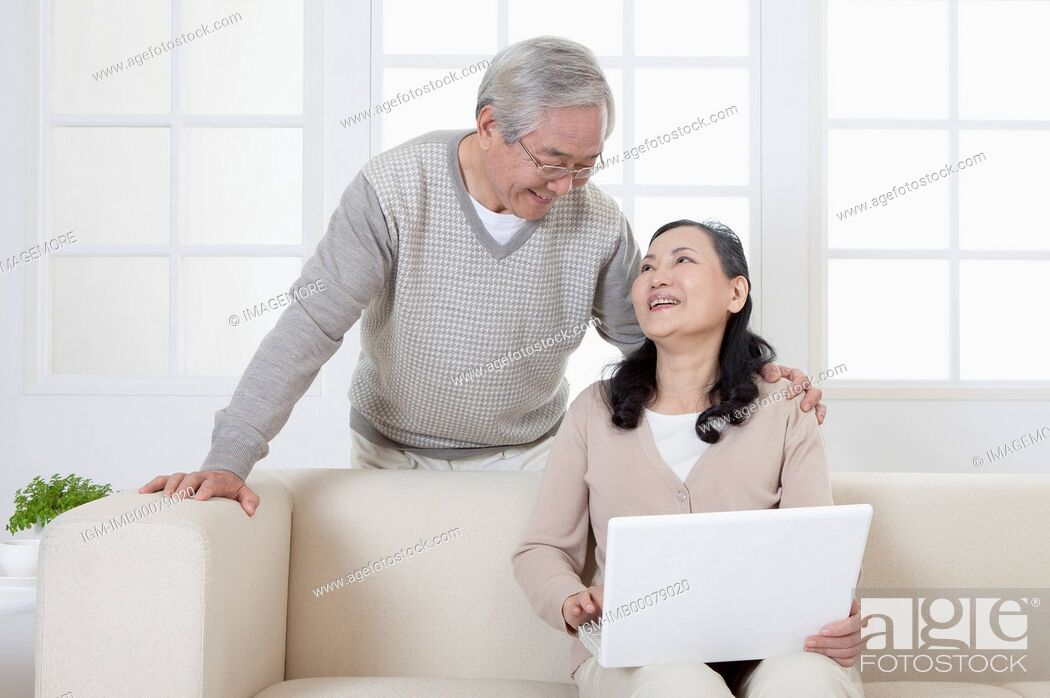 Imagen: Senior couple holding laptop and smiling happily,.