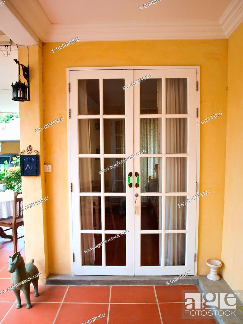 Stock Photo: Double patio white french doors with windows on yellow wall.