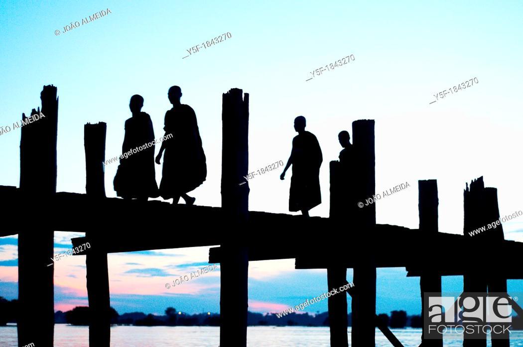 Stock Photo: People crossing the U Bein bridge by dusk.