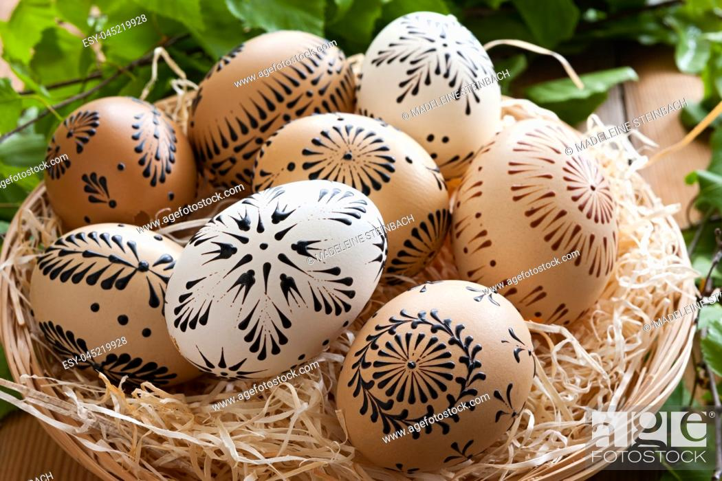 Stock Photo: Easter eggs painted with wax in a basket, with birch branches in the background.