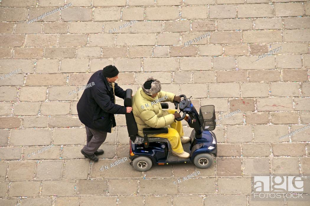Stock Photo: handicapped man being pushed in a wheelchair in Venice italy after the carnival.