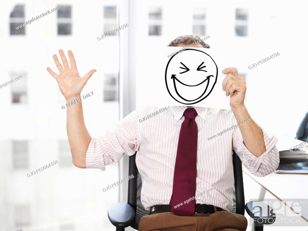 Stock Photo: Businessman holding picture of laughing face.