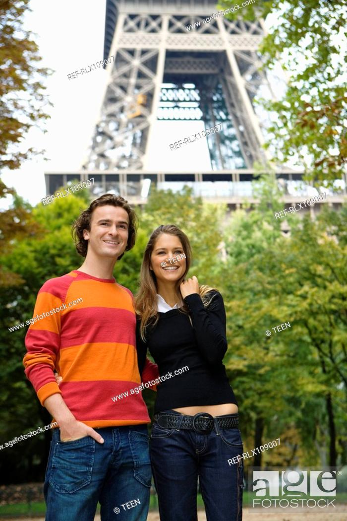 Stock Photo: Young smiling couple standing in front of Eiffel tower, Paris, France.