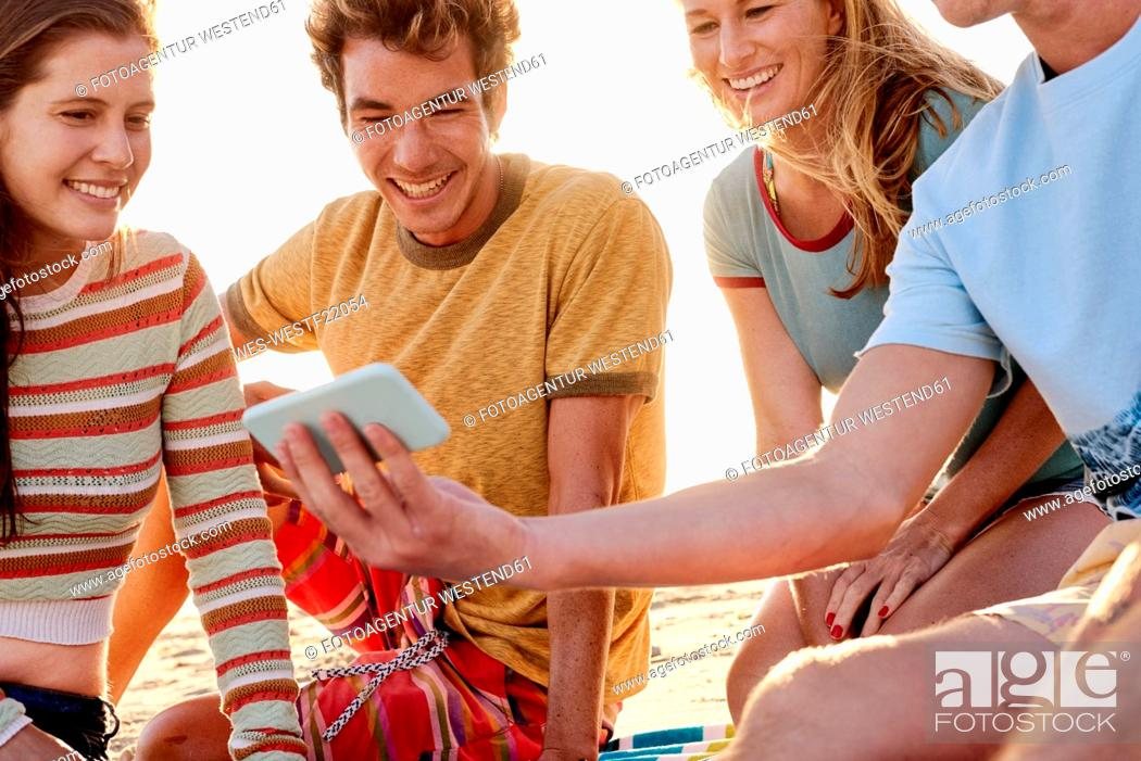 Stock Photo: Happy friends with cell phone on the beach.