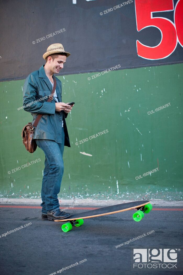 Stock Photo: Mid adult male skateboarder reading text message on smartphone.