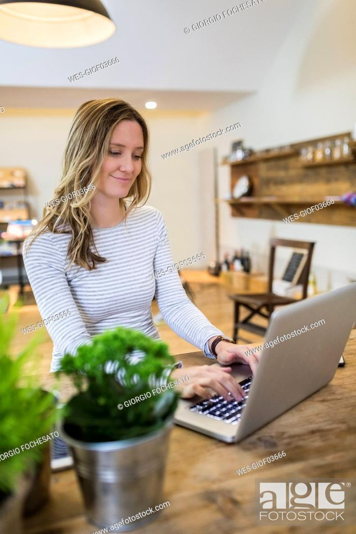 Stock Photo: Smiling woman using laptop on wooden table at home.