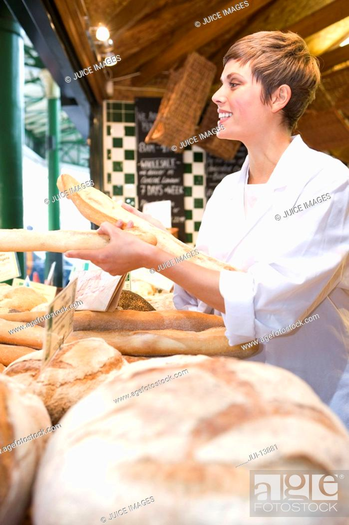 Stock Photo: Female baker with baguettes in bakery, smiling, side view.