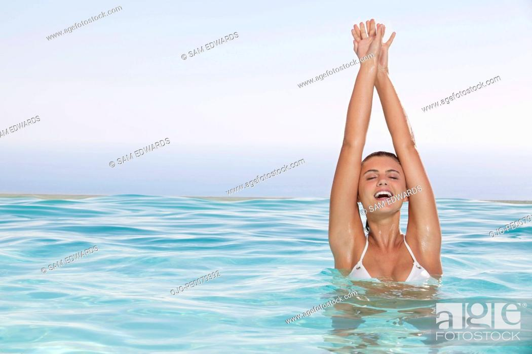 Stock Photo: Woman with arms raised in swimming pool.