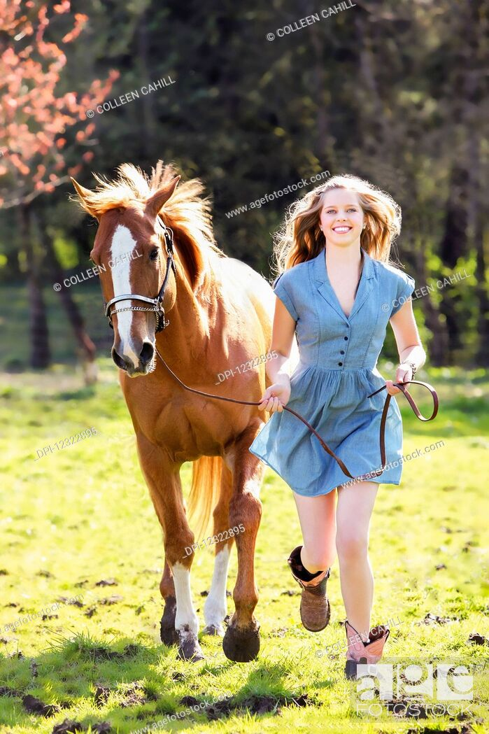Stock Photo: A young woman runs in a field with a horse; Oregon, United States of America.