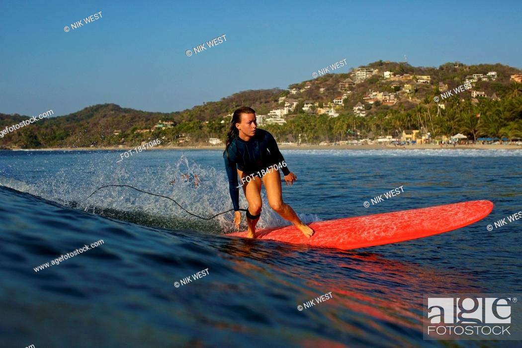 Photo de stock: Female surfer riding ocean wave, Sayulita, Nayarit, Mexico.