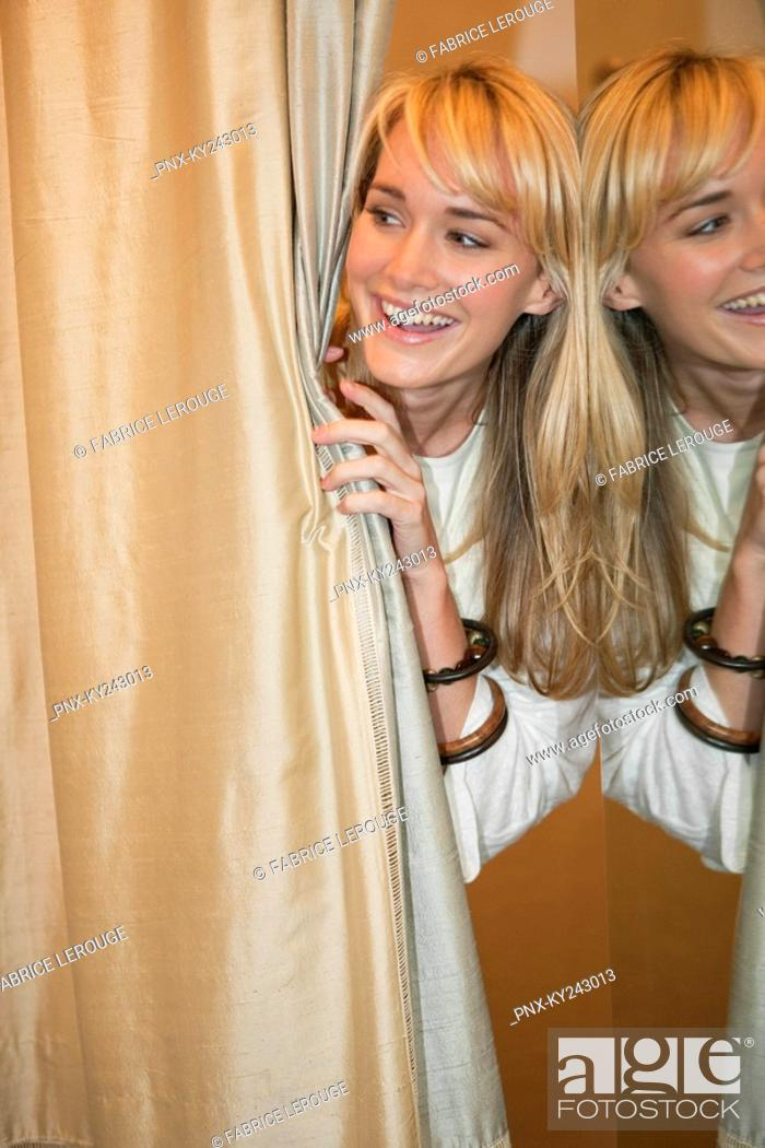 Stock Photo: Woman peeking from behind a curtain and smiling in a boutique.