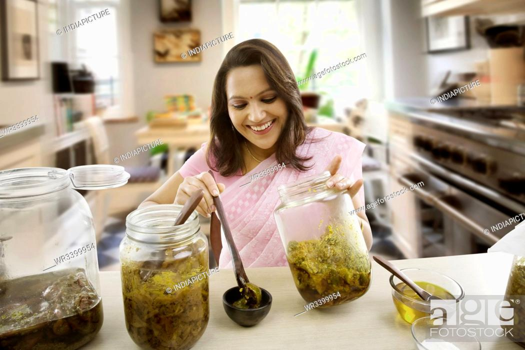 Stock Photo: Woman putting pickle into a bowl.