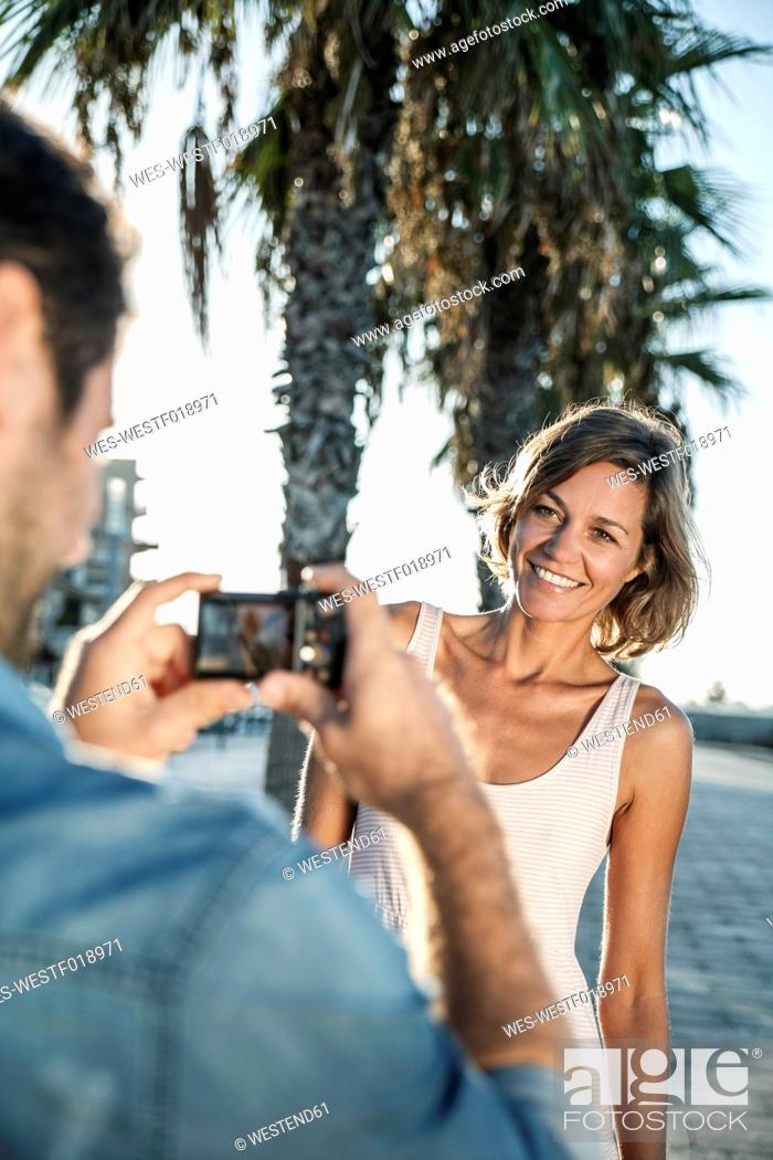 Stock Photo: Spain, Mid adult man taking photograph of woman.