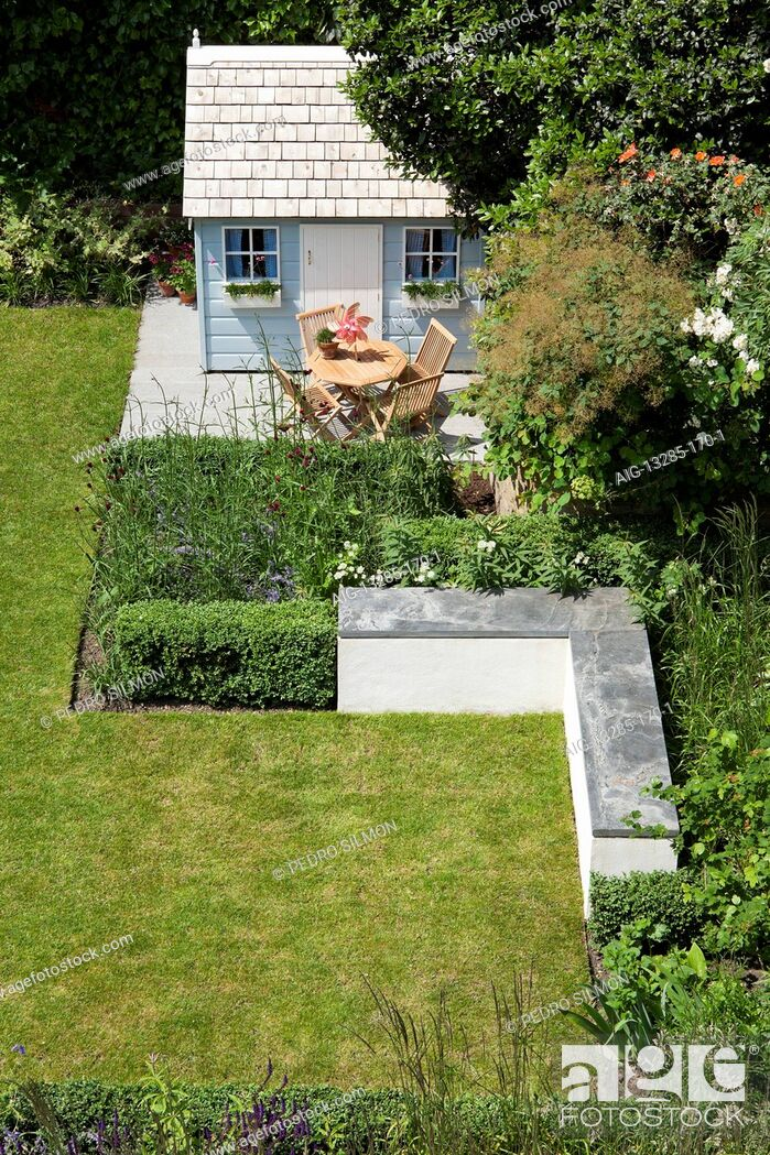 Stock Photo: Lawn, playhouse and L-shaped bench in rear garden, North London, UK., designed by Modular. Photographed in June.