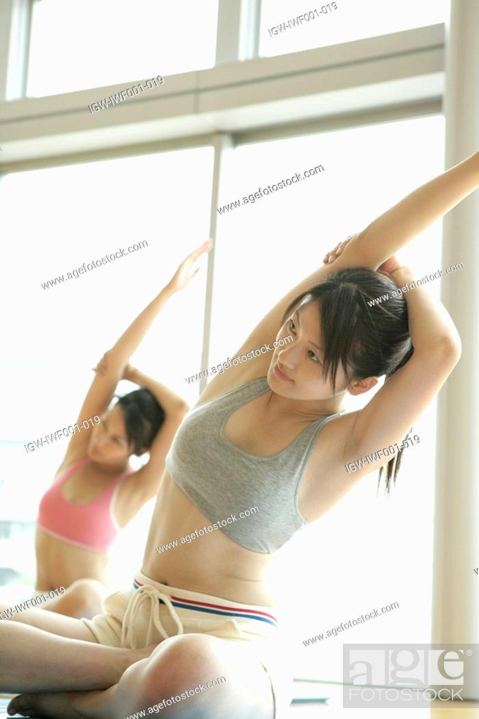 Stock Photo: Two young women stretch their arms while performing floor exercise in the gym.