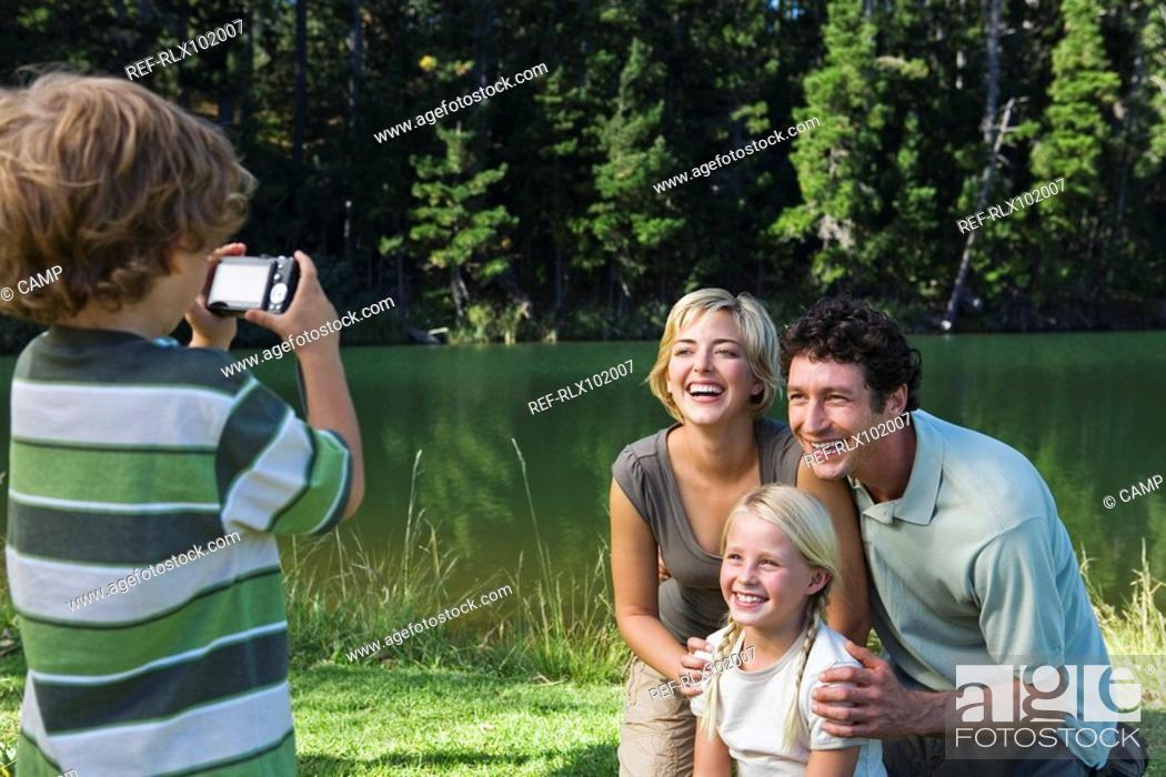 Stock Photo: Boy photographing family outdoors, mother, father and sister posing for picture.